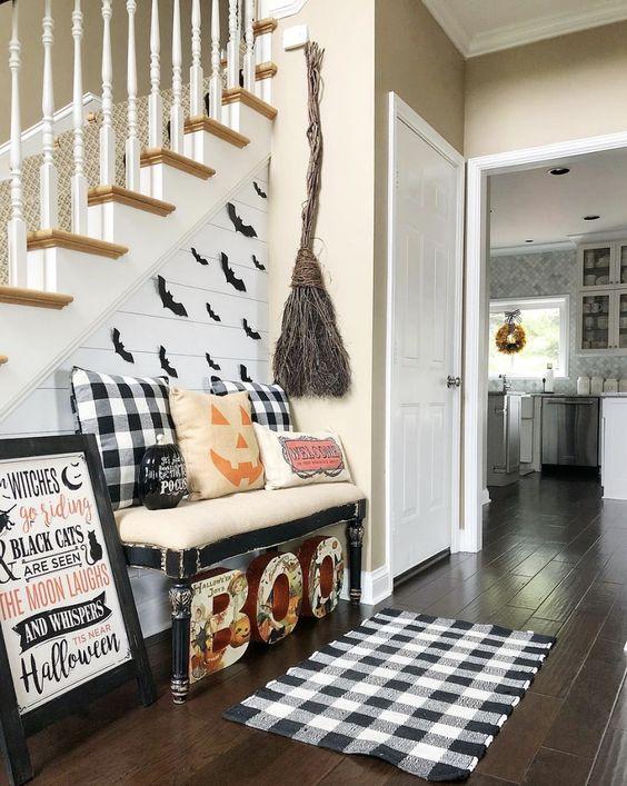 un ingresso di Halloween con lettere, elementi plaid, una scopa di ramoscelli, un cartello e alcuni cuscini di zucca