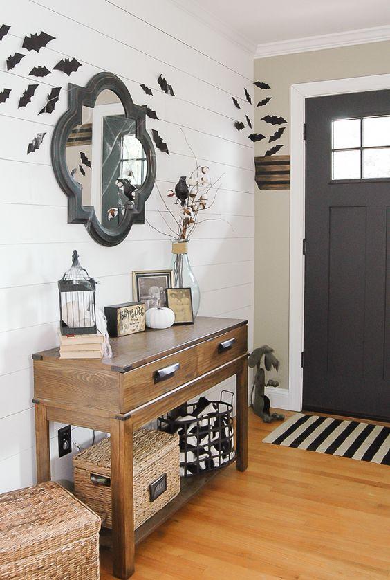 un semplice ingresso di Halloween da fattoria con pipistrelli, tocchi in bianco e nero, merli e alcune zucche bianche