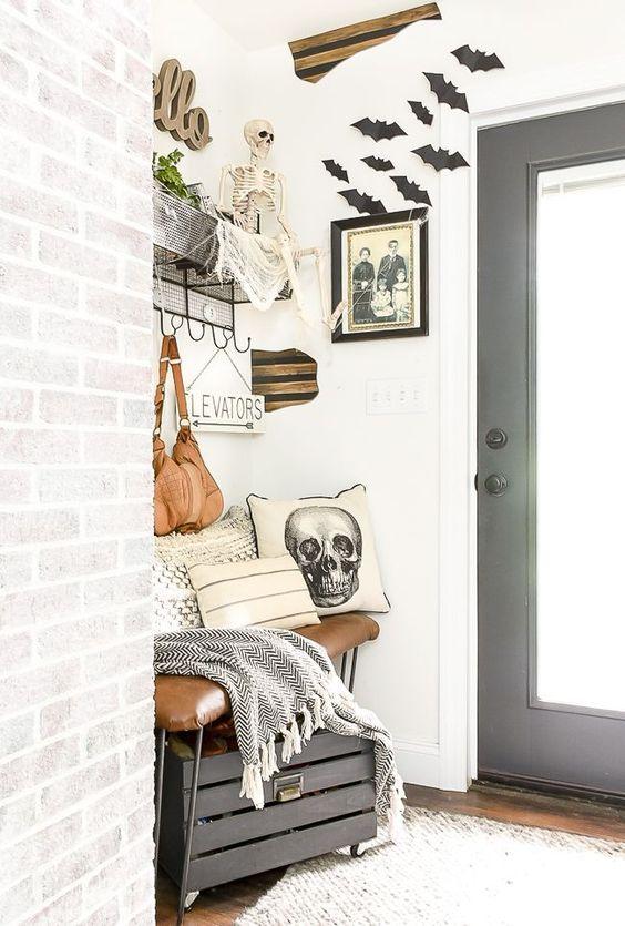 pipistrelli neri, uno scheletro, un cuscino con teschio, una foto cupa rendono questo piccolo ingresso della fattoria simile ad Halloween