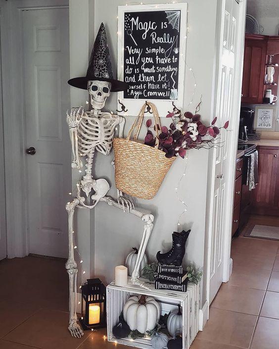 Decorazioni per l'ingresso di Halloween con uno scheletro, luci, una lanterna a candela, una creazione con zucche e una borsa di paglia con fiori scuri