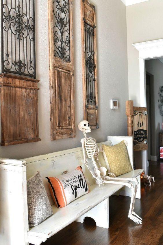 metti uno scheletro sulla panchina e alcuni cuscini ispirati ad Halloween, e hai un ingresso di Halloween