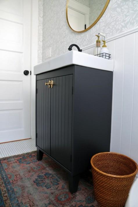 una vanità Ikea Silveran incisa con vernici nere e legno più manopole in ottone che si abbinano alla cornice dello specchio