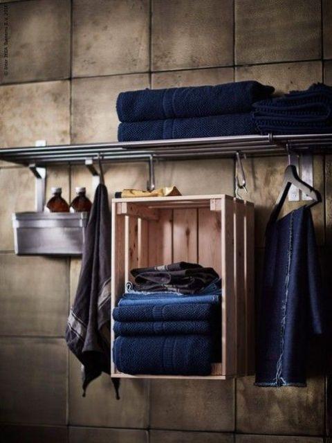 una scatola IKEA Knagglig appesa a ganci e usata come portasciugamani è un'idea creativa per aggiungere un po 'di spazio di stoccaggio
