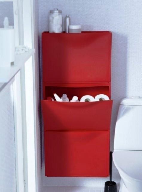 un pezzo di IKEA Trones rosso vivo attaccato al muro e utilizzato per riporre le forniture per il bagno