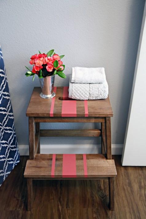 un comodo contenitore sul lato della vasca di uno sgabello Ikea Bekvam arricchito con un po 'di vernice corallo e uno stencil