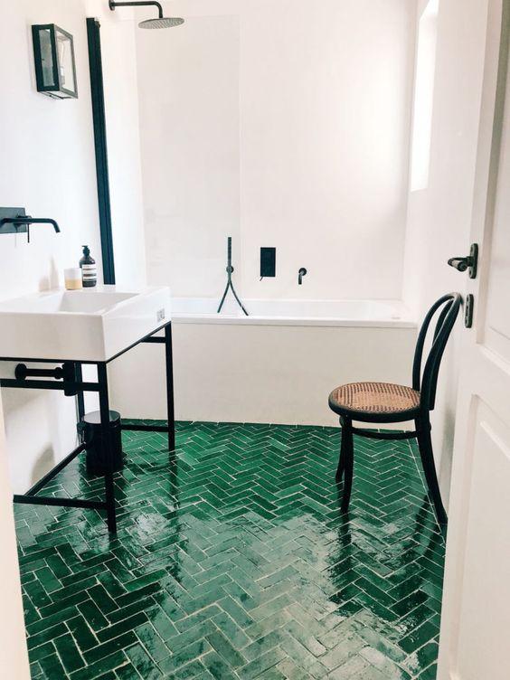 un bagno neutro arricchito con tocchi neri drammatici e un pavimento di piastrelle smeraldo con un motivo a spina di pesce
