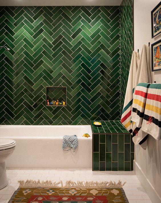 un muro di piastrelle verdi con un motivo a spina di pesce e un tocco verde aggiuntivo sulla vasca