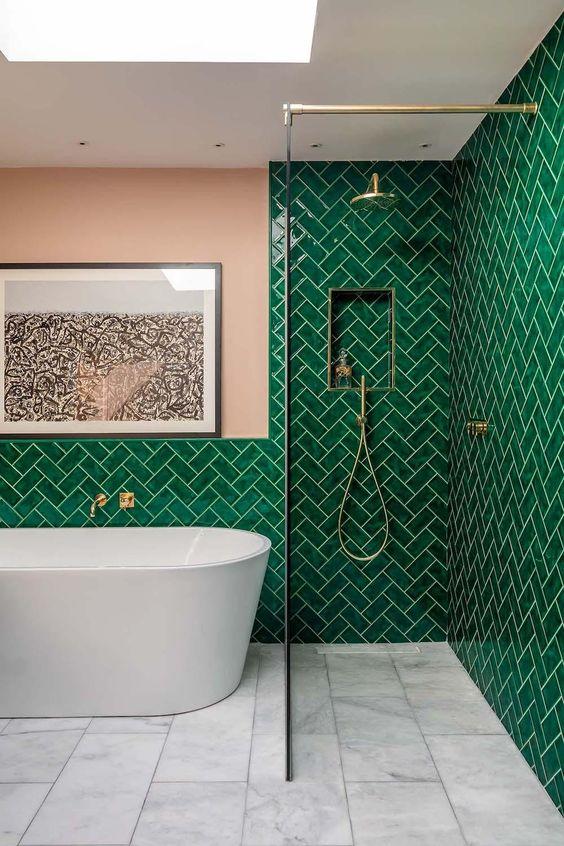 un bagno audace con piastrelle color smeraldo rivestite a spina di pesce e tocchi arrossati