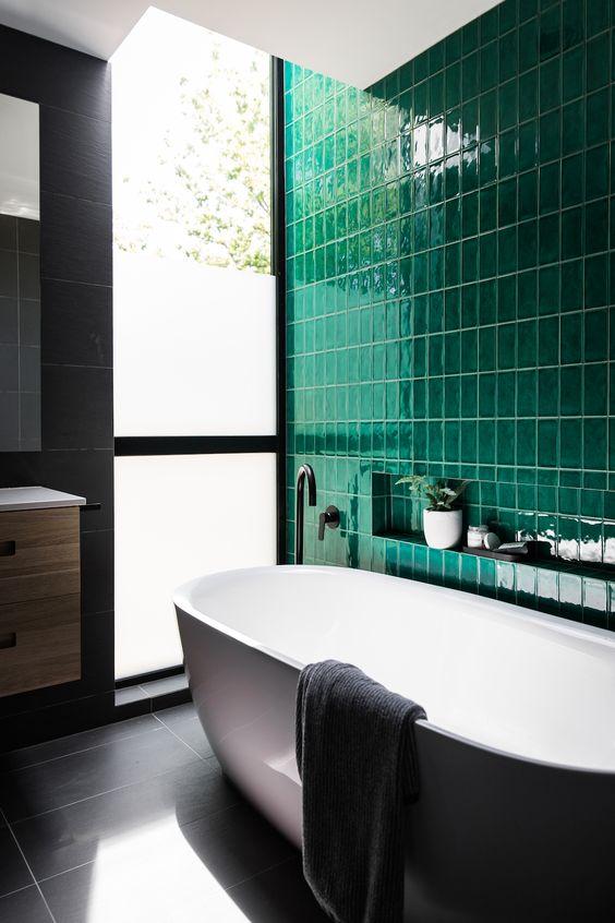 un bagno contemporaneo fatto con un muro di piastrelle smeraldo e piastrelle grigie tranquille sul resto delle superfici