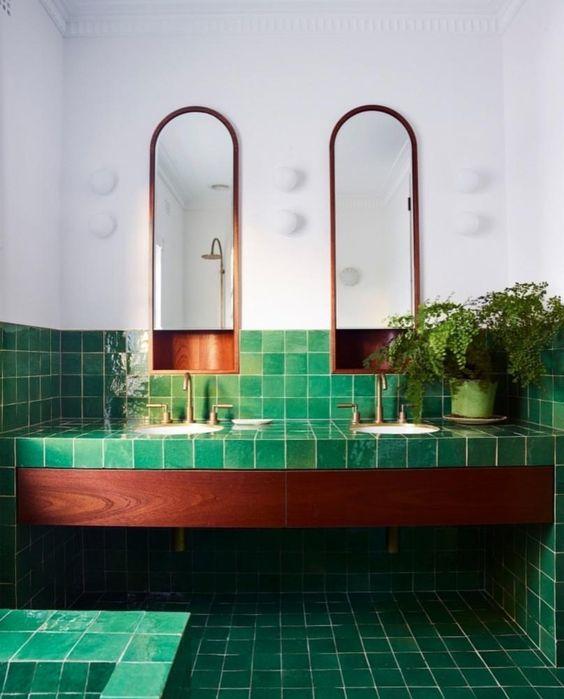 piastrelle verdi in tutto il bagno contrastano la ricca macchia del legno e tocchi di rame