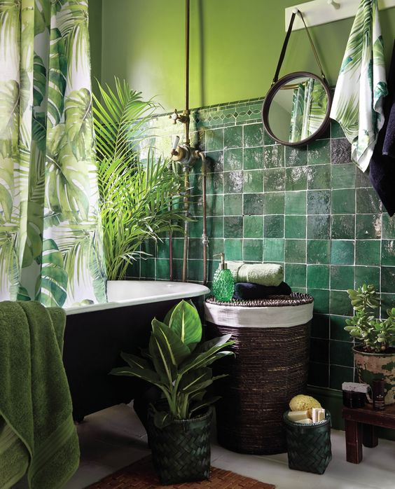 piastrelle verde scuro abbinate a pareti verde chiaro, molta vegetazione e una tenda con stampa tropicale per un'atmosfera tropicale