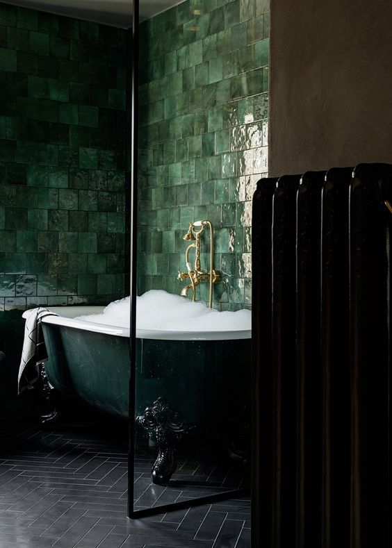 una squisita vasca da bagno con piedini verde scuro circondata da piastrelle verdi lucide alle pareti