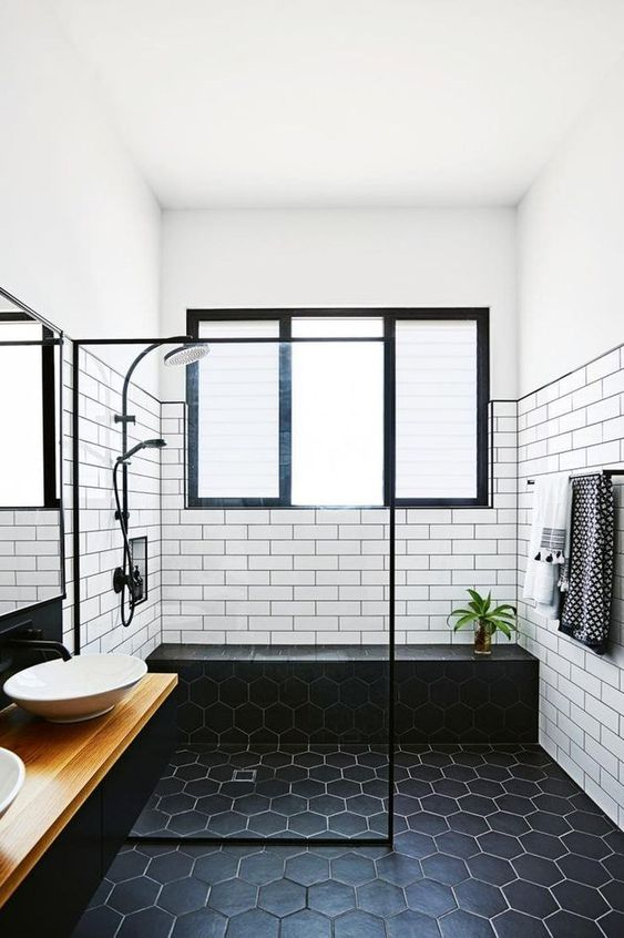 un elegante bagno in bianco e nero fatto con piastrelle bianche della metropolitana e quelle nere esagonali