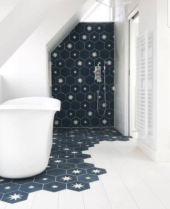 un laconico bagno fatto con piastrelle bianche e piastrelle esagonali blu scuro con stelle che vengono sotto la vasca