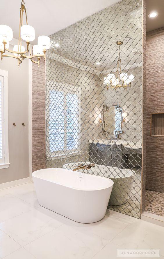 un muro fatto con piastrelle marocchine riflettenti separa la vasca dal resto dello spazio e lo accentua