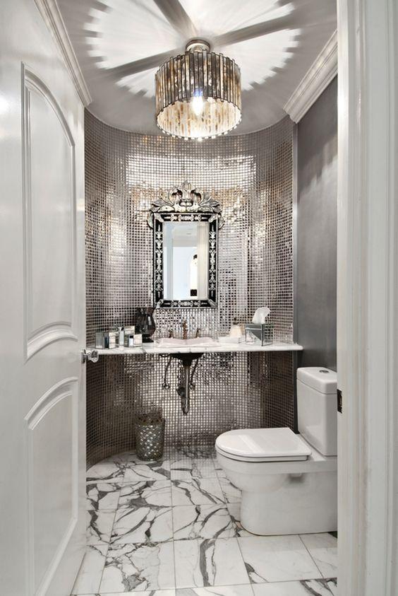 un mudroom glam con lucide piastrelle riflettenti, un pavimento in marmo e una raffinata cornice di specchio