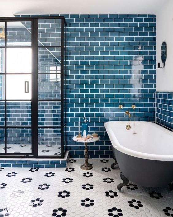 le luminose piastrelle verde acqua sul muro sono accentate con malta bianca e un pavimento in piastrelle esagonali aggiunge interesse
