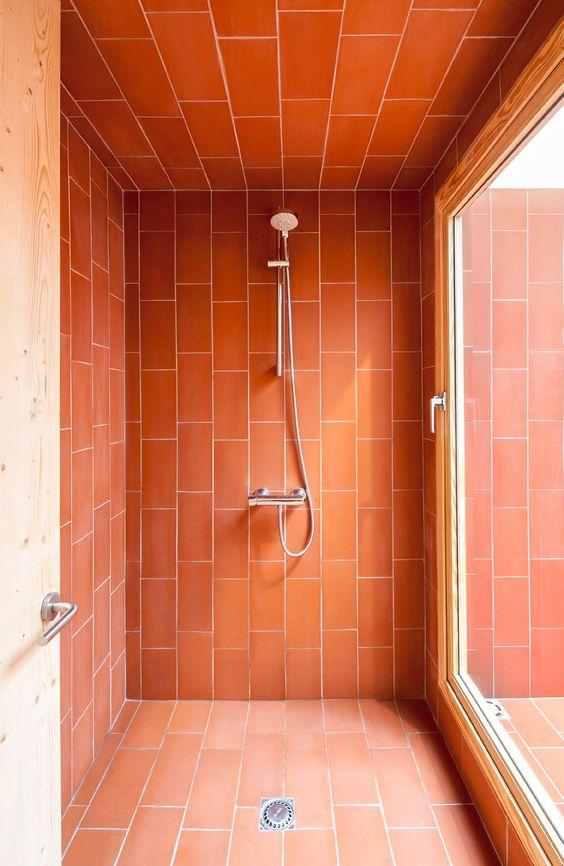 uno spazio doccia accentuato con brillanti piastrelle di corallo per farlo risaltare in bagno