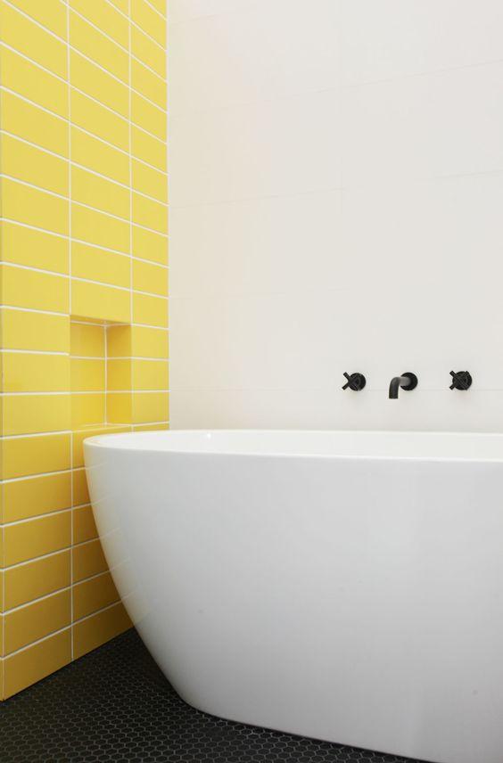 un bagno minimalista con un muro di piastrelle gialle e una vasca da bagno neutra ed elegante