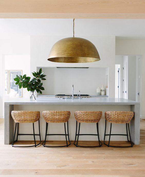 una lampada a sospensione in metallo di grandi dimensioni riecheggia con le sedie in rattan e porta consistenza