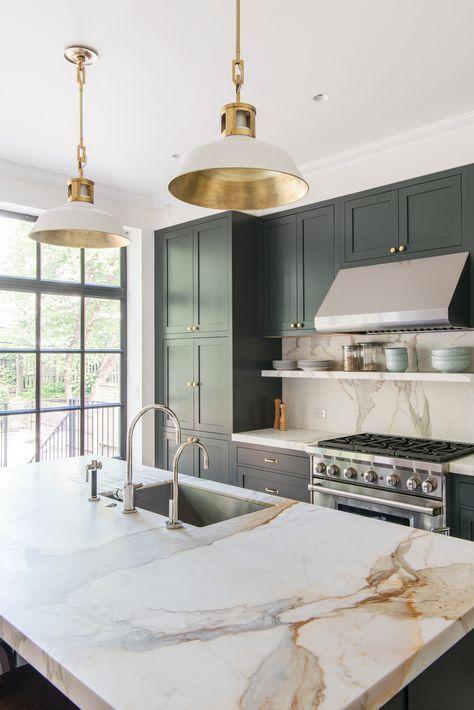 eleganti lampade a sospensione bianche con tocchi d'oro accentuano la cucina ed echeggiano con l'hardware d'oro usato qui