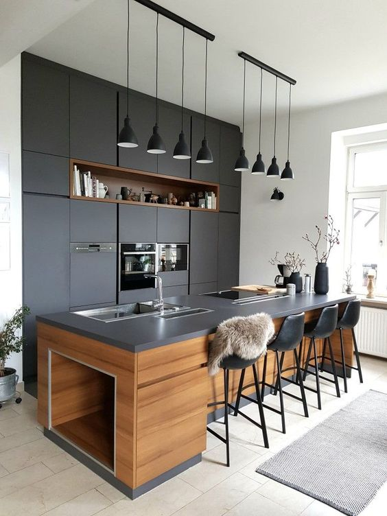 una cucina scura super chic con lampade a sospensione blakc abbinate appese in fila è un'idea fresca e audace