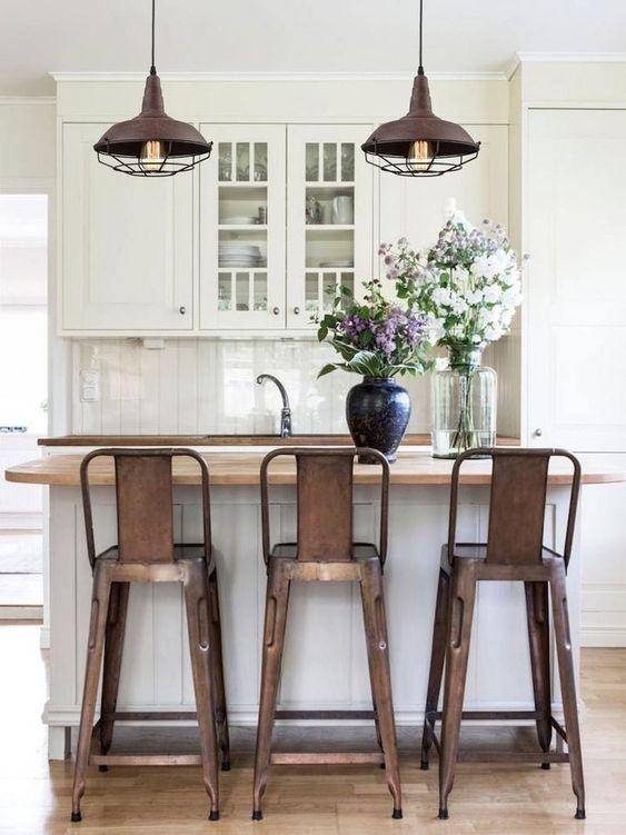 stupende lampade a sospensione in metallo invecchiato che riecheggiano con gli sgabelli e creano un'atmosfera in cucina