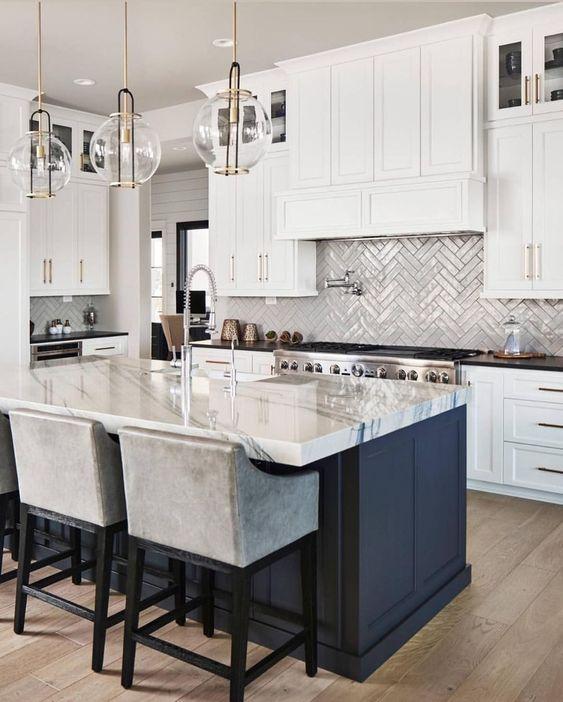 le eleganti lampade a sospensione a bolle di vetro con tocchi dorati aggiungono eleganza alla cucina e fanno eco con l'hardware