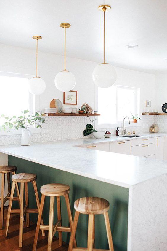 le lampade a sospensione bubble in vetro bianco continuano lo stile d'arredo della cucina conferendogli una sensazione di leggerezza