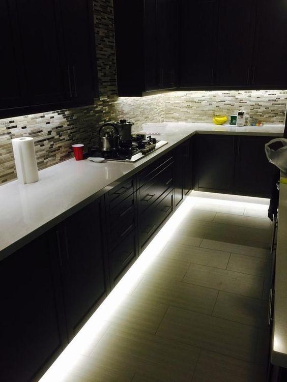 una cucina buia con luci sotto l'armadio e luci sopra il piano di lavoro come illuminazione ambientale