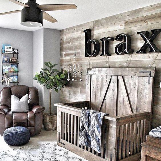 un accogliente cameretta della fattoria, una parete in legno di recupero e una culla abbinata, un nome sul muro, una sedia in pelle e un ventilatore