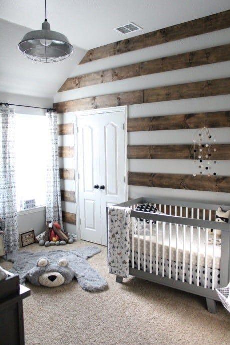 un elegante cameretta nel bosco con un muro di legno tinto a strisce, tappeti a strati, una culla vintage grigia, una lampada a sospensione e tende di pizzo