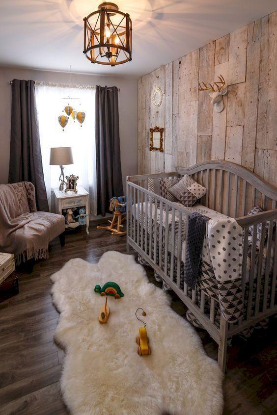 un bel cameretta rustico con una parete in legno di recupero, una grande culla grigia, un soffice tappeto, tende scure e un lampadario vintage