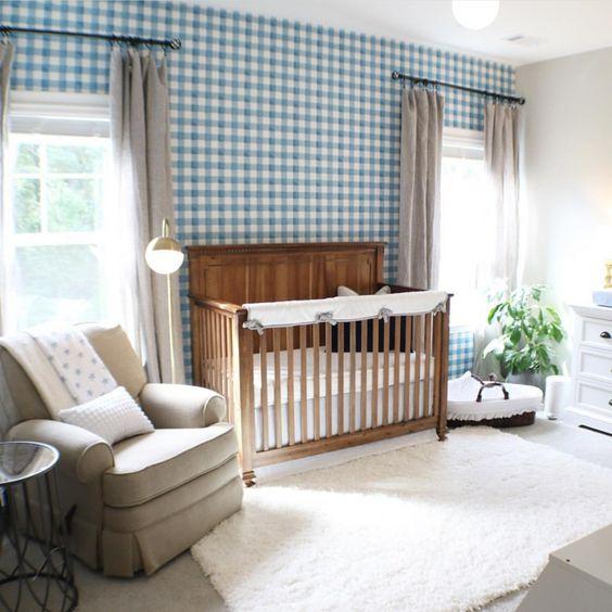 un grazioso cameretta con un muro scozzese blu, una culla macchiata, mobili vintage, tende grigie e un tappeto color crema