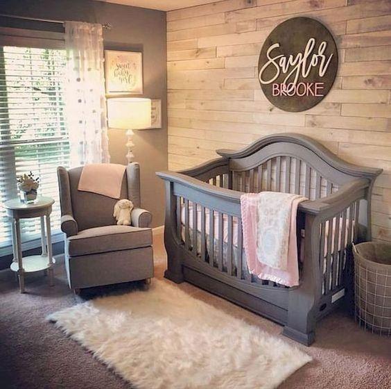 un accogliente spazio di una piccola fattoria con una parete in legno di recupero, una culla e una sedia grigie, un soffice tappeto e sfumature sulla finestra