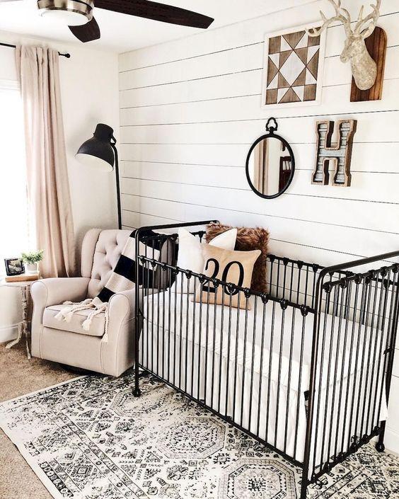 un accogliente cameretta con un muro a battente, una culla di metallo nero, un tappeto stampato, una sedia arrossata e tende arrossate oltre a tocchi di nero per il dramma