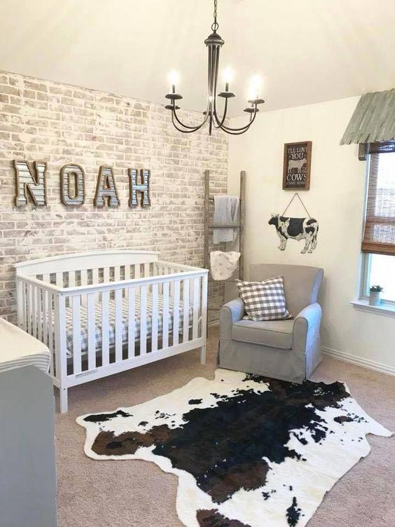 un cameretta di fattoria con un muro di mattoni imbiancato, un tappeto di pelle di animale, mobili grigi e un lampadario vintage