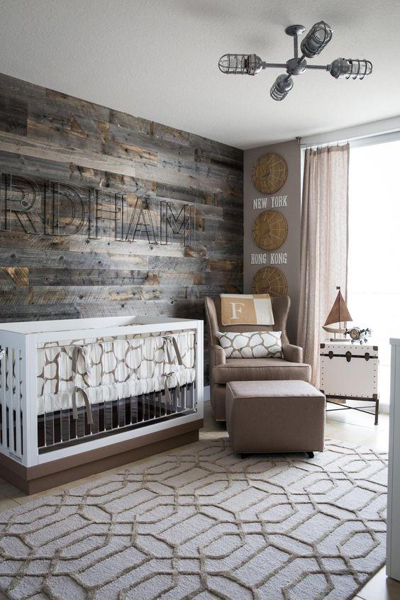 un cameretta moderno con una parete in legno di recupero, una sedia e un poggiapiedi color talpa, una culla moderna con acrilico e un tappeto stampato