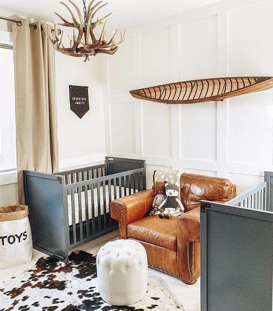 un cameretta in comune con culle grigie, una sedia in pelle, un lampadario di corno e un tappeto di pelle di animale