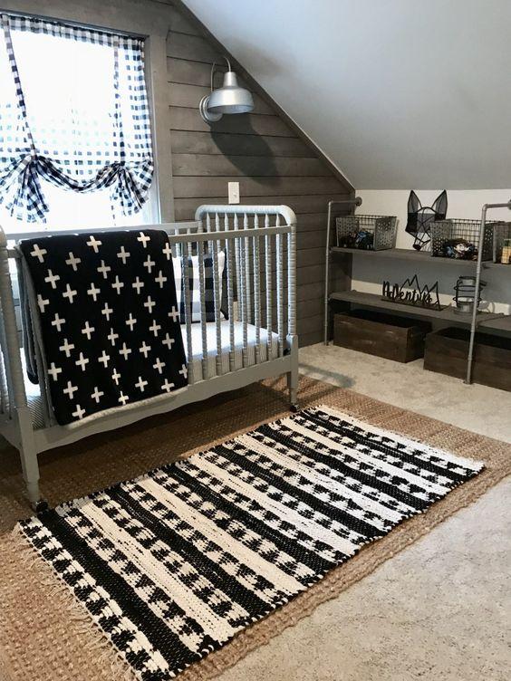 un piccolo cameretta mansardato con un tappeto di iuta, uno stampato, un presepe vintage grigio, stampe e una parete in legno di recupero