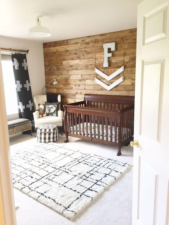 un cameretta rustico con un tappeto stampato, una culla macchiata, un muro di recupero e alcuni tocchi di stampe
