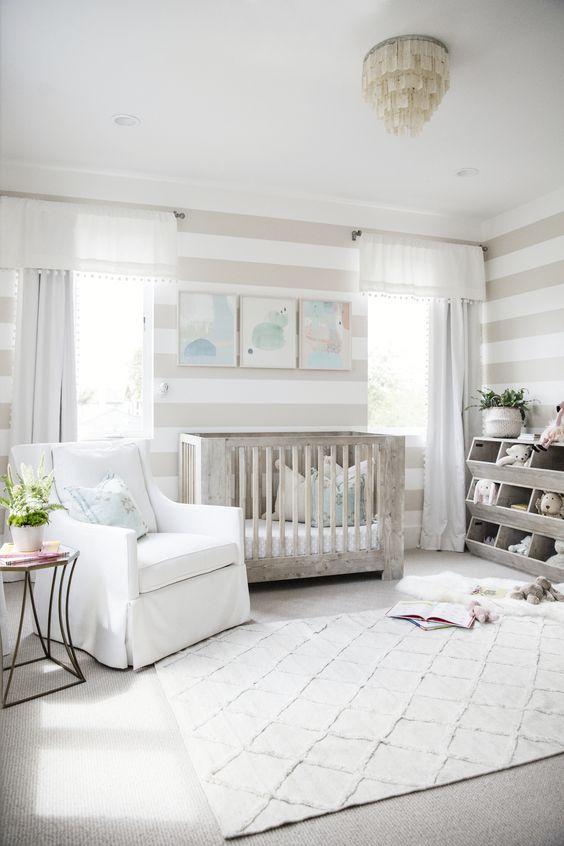 un cameretta neutro con una culla imbiancata a calce, un lampadario unico, un tappeto stampato e strisce sulle pareti