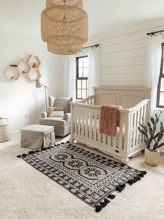 un cameretta vintage con un muro bianco, un tappeto stampato, una culla vintage grigia e una fioriera sospesa