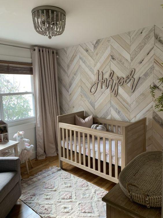 un caldo cameretta neutro con una parete in legno di recupero con un motivo a spina di pesce, un lampadario di perline, un tappeto fresco e una culla macchiata