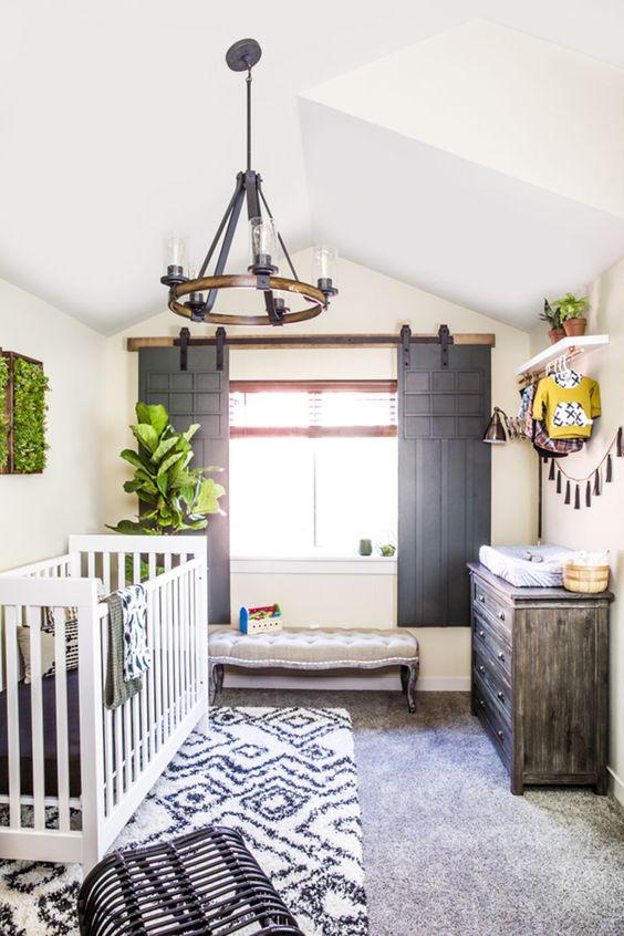 un cameretta di fattoria unico con persiane scorrevoli di porte vintage, un crub bianco, tappeti a strati stampati e un lampadario vintage
