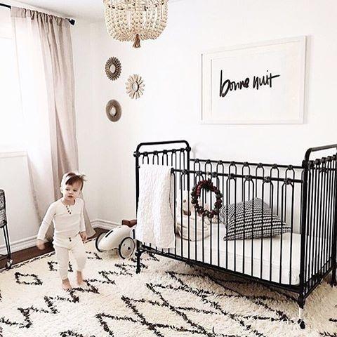 un cameretta in bianco e nero con un tappeto stampato, un letto nero, un lampadario di perline e una semplice opera d'arte