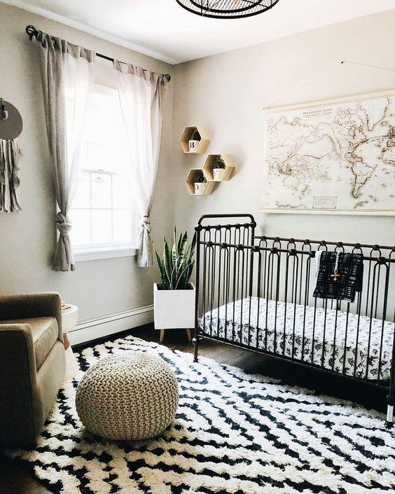 un cameretta in bianco e nero con un tappeto stampato, mensole esagonali e una mappa più una sedia e un poggiapiedi neutri