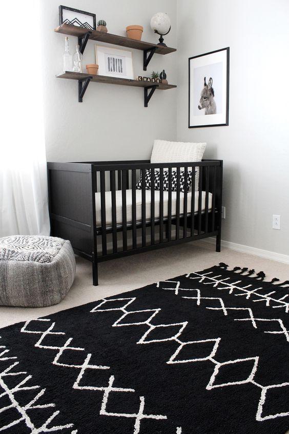 un cameretta chic con una culla nera, un tappeto stampato, mensole in legno e una bella opera d'arte per uno spazio semplice e accogliente