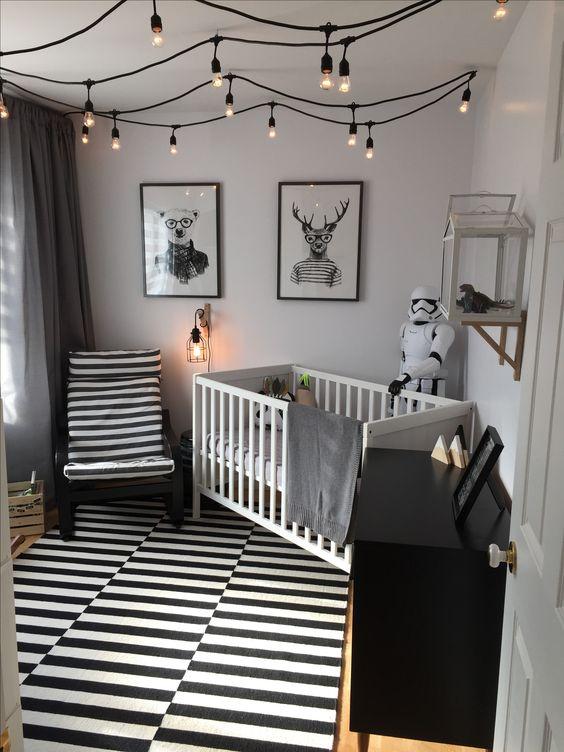 un cameretta monocromatico con un tappeto e una sedia a righe, un comò nero, una culla bianca e lampadine attaccate al soffitto