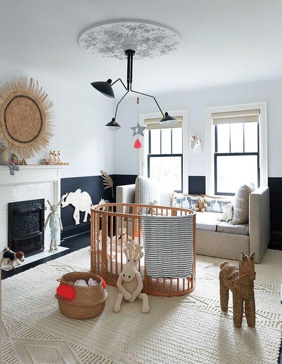 un raffinato cameretta in bianco e nero con un tappeto neutro, un divano e una culla in legno più cestini